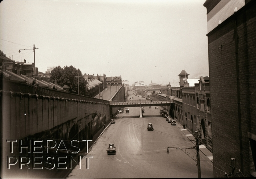 View south along Hickson Road from bride at Munn Street, showing how uplands border Darling Harbour restricting expansion of ware houses etc. Dock sheds at right and residences facing High Street on cliff top at left